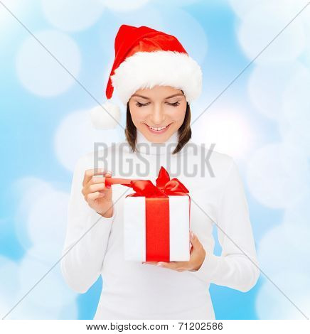christmas, winter, happiness, holidays and people concept - smiling woman in santa helper hat with gift box over blue lights background