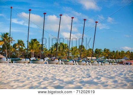 Group of catamarans with colorful sails on exotic Caribbean beach