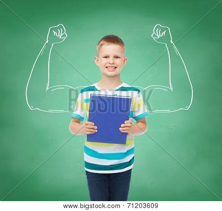 education, childhood and school concept - smiling little student boy with book over green board background strong arms drawing