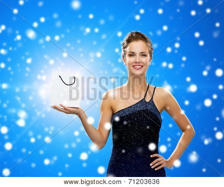 advertisement, winter holidays, christmas and sale concept - smiling woman with white blank shopping bag over black background over blue snowy background