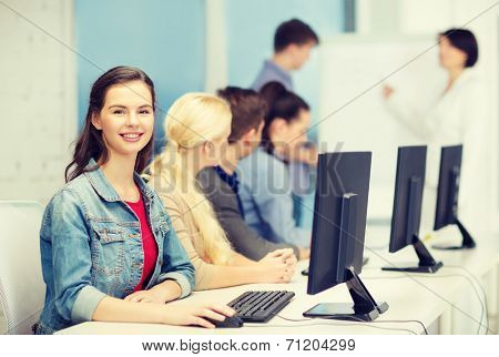 education, techology, school and internet concept - smiling teenage girl in computer class with classmates and teacher