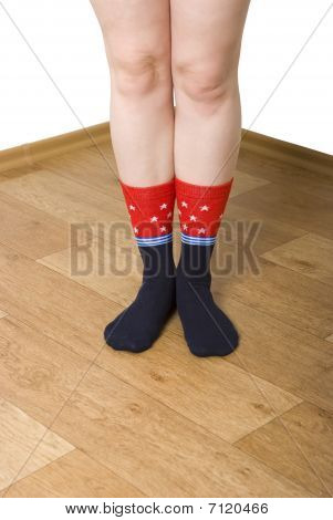 Legs In Socks On A Wooden Floor
