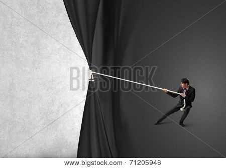 Young businessman pulling curtain with rope. Place for text