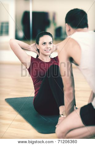 fitness, sport, training, gym and lifestyle concept - male trainer with woman doing sit ups