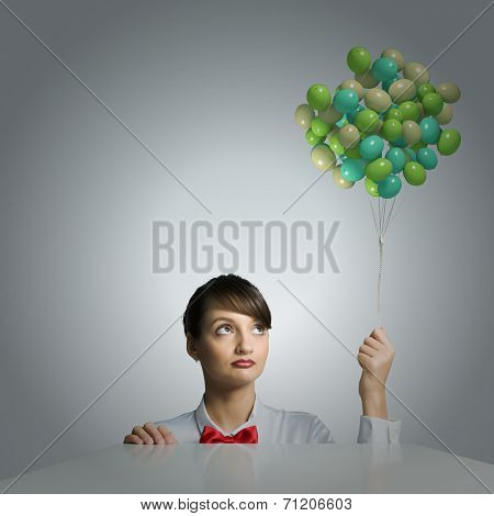 Young attractive businesswoman holding bunch of colorful balloons