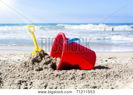 While playing in the water, a child??s toy plastic bucket and shovel are left in the sand during a summer holiday.