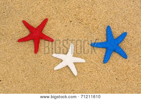 Conceptual summer holiday image of three red, white and blue starfish on smooth sand representing patriotism and the Fourth of July holiday.