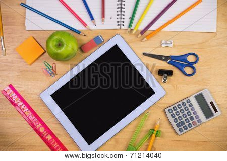 Students table with school supplies and tablet pc