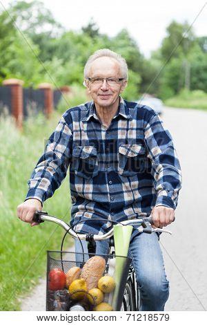 Smiling Senior Man Riding A Bicycle