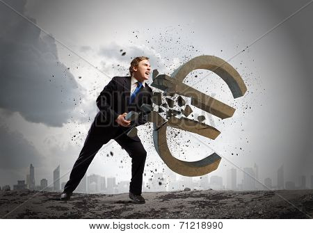 Young businessman breaking stone euro sign. Currency concept