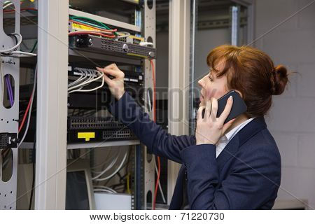 Pretty computer technician talking on phone while fixing server in large data center