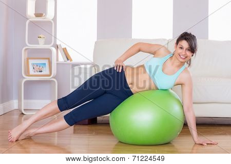 Fit brunette in plank position on exercise ball at home in the living room
