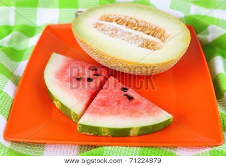 Water melon and melon on orange plate on  green tablecloth
