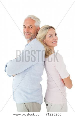 Smiling couple standing leaning backs together on white background
