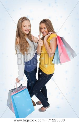 Two beautiful young women with shopping bags the thumbup against night sky