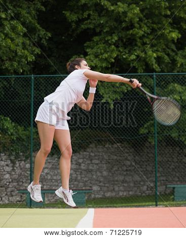 Pretty tennis player jumping and hitting on a sunny day