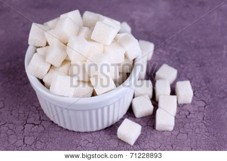 Refined sugar in bowl on color wooden background