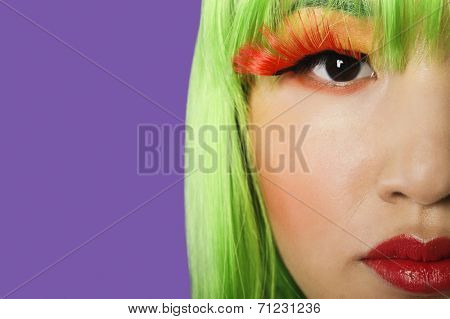 Cropped image of young woman wearing false eyelashes against purple background