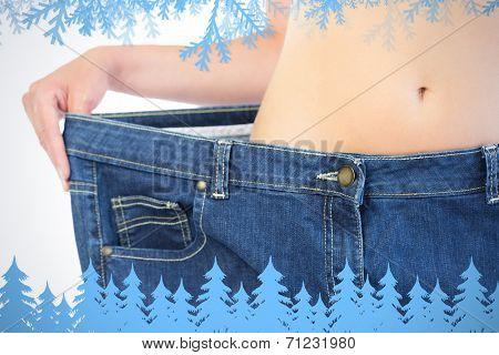 Extreme close up of confident slender blonde wearing too big trousers against frost and fir trees in blue