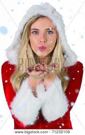 Pretty girl in santa outfit blowing against snow falling
