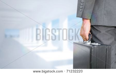 Businessman holding briefcase against bright white room with columns