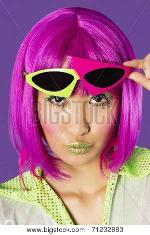 Portrait of young funky woman in pink wig puckering lips over purple background