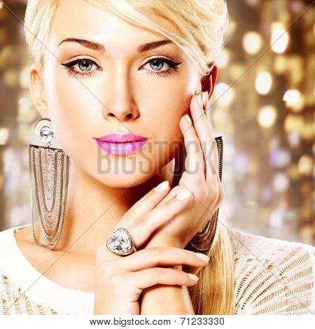 Portrait of a beautiful woman with bright pink lips and  fashion makeup. Model posing at studio on the art background