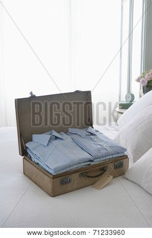 Ironed and folded shirts in open suitcase on bed