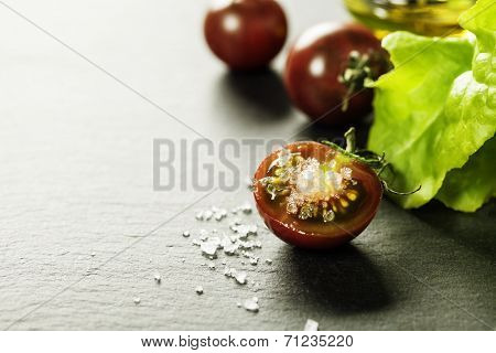 Fresh grape tomatoes with salad leaves and salt for use as cooking ingredients with a halved tomato in the foreground with copyspace