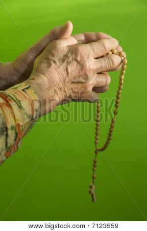 hand of old woman by prayer of rosary