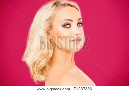 Beautiful haughty young blond woman standing sideways with bare shoulders looking at the camera with parted lips
