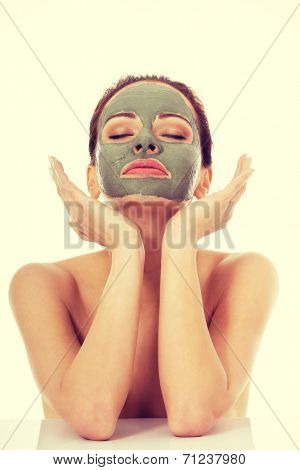 Beautifu toplessl woman with facial mask having her eyes closed. Isolated on white.