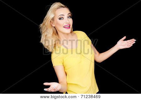 Young blond woman showing her ignorance smiling as she holds out her hands palm upwards to show she does not know or care  on black