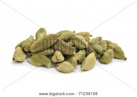 a pile of green cardamom seeds on a white background