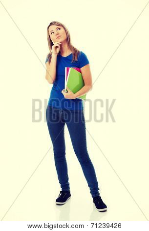 Young casual female student with workbook is thinking. Isolated on white.