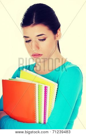 Portrait of young sad female student with workbook. Isolated on white.