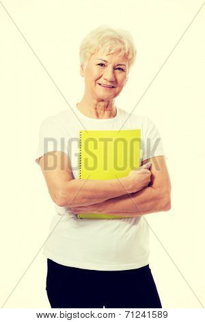 An old woman holding a workbook. isolated on white.