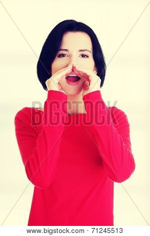 Pretty caucasian woman whispering gossip. Isolated on white.