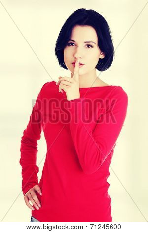 Woman making a keep it quiet gesture , isolated on white