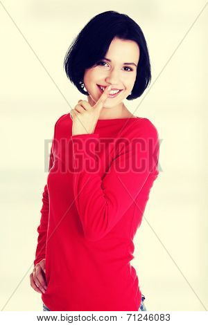 Happy woman making a keep it quiet gesture , isolated on white