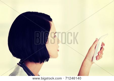 Female doctor or nurse checking temperature of her patient