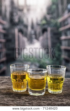 glass shots with yellow liqour resembling whiskey, rum, tequila, spirit