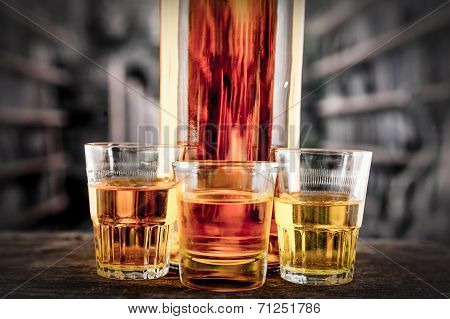 Bottle and glass shots with yellow liqour resembling whiskey, rum, tequila, spirit