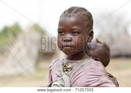 TORIT, SOUTH SUDAN-FEBRUARY 21 2013: An unidentified little girl responsible for carrying her baby sister in Torit, South Sudan