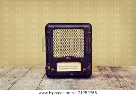 Retro radio on a wooden floor over vintage wallpaper