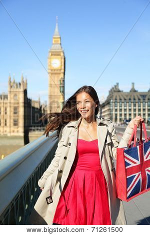 London woman tourist shopping bag near Big Ben. Happy woman shopper smiling happy during tourism travel vacation in London. Multicultural Asian Caucasian female traveler on Westminster Bridge.