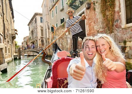 Travel concept - happy couple Venice gondola giving thumbs up hand sign excited looking at camera. Romantic young beautiful couple on vacation holidays sailing in venetian canal in gondole. Italy