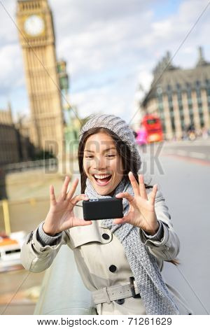 Travel tourist in london sightseeing taking selfie photo pictures near Big Ben. Woman holding smart phone camera smiling happy near Palace of Westminster, Westminster Bridge, London, England