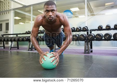 Determined shirtless muscular man doing push ups with ball in the gym
