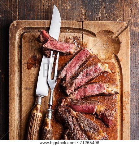 Medium Rare Beef Steak Ribeye With Knife And Fork For Meat On Cutting Board On Dark Wooden Backgroun